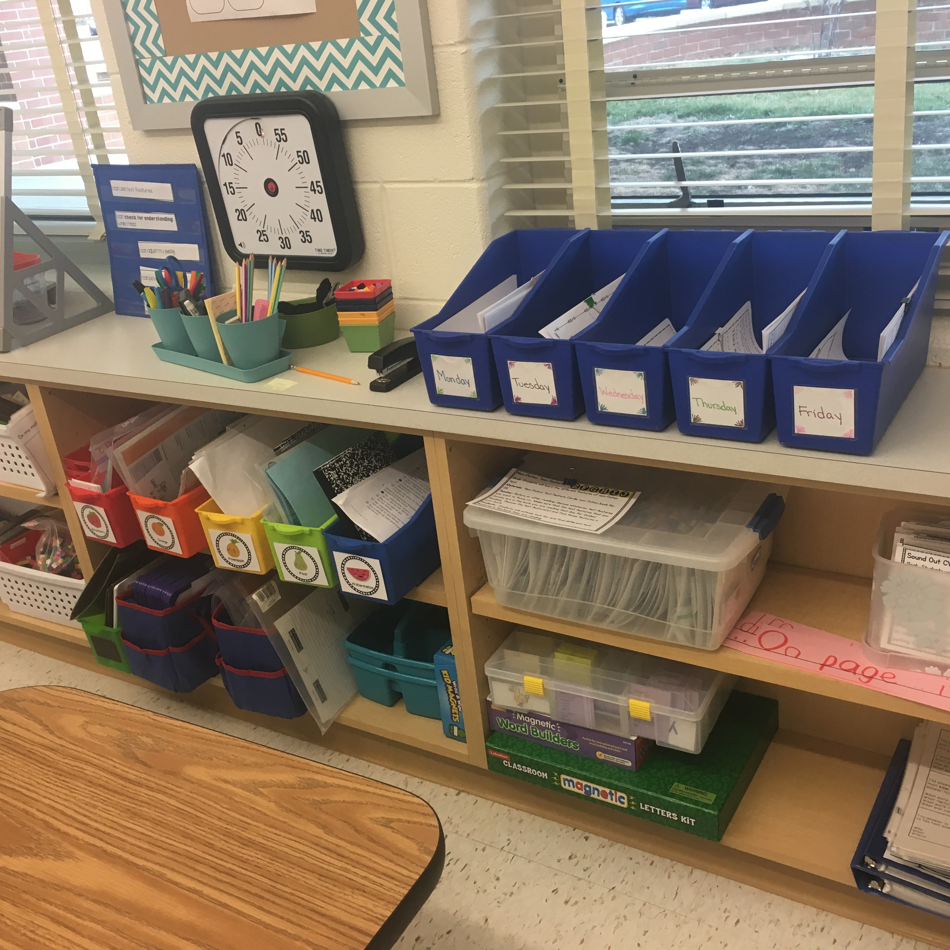 classroom with blue bins and rainbo color bins used to organize papers.