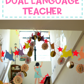 "Going upstairs in a school with decorations on the ceiling with text"" Secrets of a dual language teacher"""