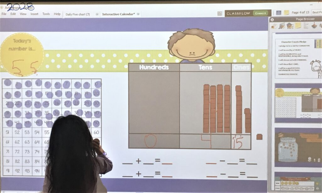 Girl using a 100 chart and place value chart to show the number of the day as part of the interactive math calendar activity.