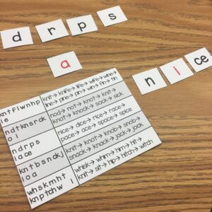 Chaining card example with lists of words and letter cards on top of the table. Cards are placed next to the paper to make the word: NICE.